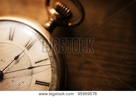 Old pocket watch on grungy wooden desk. Shot in low key and extremely shallow depth for impressional