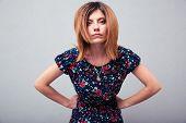 foto of disapproval  - Portrait of angry woman looking at camera over gray background - JPG