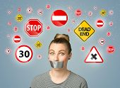 picture of taboo  - Young woman with taped mouth and traffic signals around her head - JPG