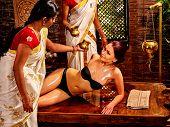 stock photo of panchakarma  - Young woman having pouring oil Ayurveda spa treatment - JPG