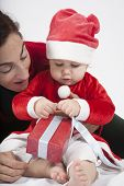 image of santa baby  - one year age caucasian blonde baby Santa Claus disguise with brunette woman mother red cardigan green trousers opening Christmas box gift on white background - JPG