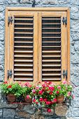 stock photo of stone house  - Typical window of an Italian stone house with wooden shutters closed and colorful flowers on the windowsill - JPG