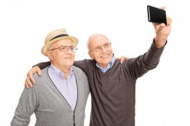 image of cell  - Studio shot of two senior men taking a selfie with cell phone and smiling isolated on white background - JPG