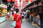 Woman tourist walking in chinatown on china travel. Asian girl on Wangfujing food street during Asia poster