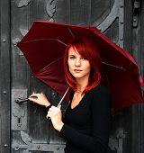 schönes Mädchen unter roten Dach in der Nähe der alten Tür