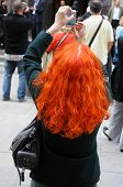 Red-haired woman taking photo with cellphone