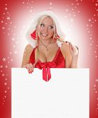 sexy blond mrs. Santa holding white billboard