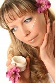 beautiful adult woman applying cream on her face