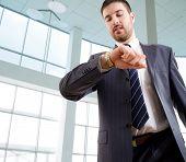 Empresario mirando el reloj de pulsera en la oficina