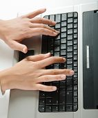 Vertical image of human hands doing some computer work