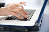 Photo of female hands typing a letter on the laptop