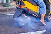 image of noise pollution  - Moped rider polluting the environment with smog - JPG