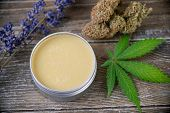 Cannabis hemp cream with marijuana leaf, lavender and nugs over wood background - cannabis topicals  poster