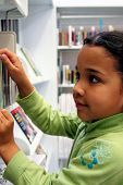 stock photo of storytime  - Child in a school library looking for books - JPG