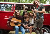 Group of young hippies men and women having fun and playing guitar near vintage minivan into the nat poster