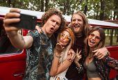 Group of lovely hippies men and women smiling and taking selfie on mobile phone near vintage minivan poster