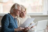 Happy Aged Couple Satisfied With Easy Online Banking Using Lapto poster