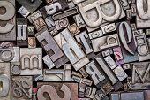background of random vintage letterpress metal type printing blocks poster