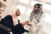 Young Arabian Man Giving Cup To Wife On Wheelchair. Arabian Family Concept. Sitting On Wheelchair. D poster
