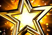 shiny gold star against orange fireworks background