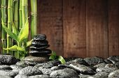 stock photo of spa massage  - spa concept bamboo grove and black zen stones on the old wooden background - JPG