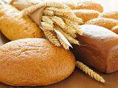 Постер, плакат: нарезанный хлеб и пшеницы на деревянный стол