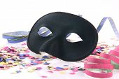 stock photo of mardi-gras  - carnival concepts paper closeup black mask with confetti and streamers isolated on white background - JPG