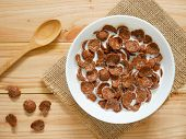 Chocolate Breakfast Cereal In A White Bowl On Wooden Table. Top View. Healthy Breakfast Concept. poster