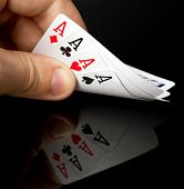 stock photo of ace spades  - Four aces in the hand with reflection - JPG