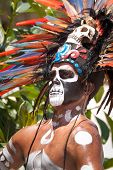 TULUM, MEXICO - JULY 15: Unidentified man in Mayan traditional ornamental feather headdress playing