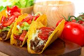Mexican burrito in tortilla shells with fresh tomatoes, cheese and lettuce