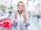 Young blonde doctor woman over isolated background smiling crossing fingers with hope and eyes close poster
