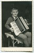 pic of aerophone  - Vintage photo of boy playing an accordion  - JPG