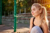 Young Woman Athlete Having Rest After Running On Sportsground In Summer. Girl Chilling Outdoors In T poster