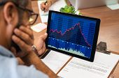 Closeup of a stock market broker working with graphs on digital tablet at office. Rear view of stock poster