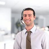 Guapo joven sonriente con un auricular