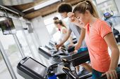 Young And Beautiful Lady Running On A Treadmill And Sweating poster