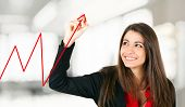Beautiful young businesswoman drawing a red business graph