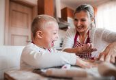 A Laughing Handicapped Down Syndrome Child With His Mother Indoors Baking. poster