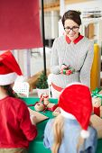 Young mother in casualwear showing her little daughters small giftbox with xmas surprise poster
