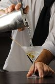 Hands, pouring a Martini cocktail. Bartender pouring liquor, Barman pouring a drink.