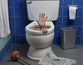 Hand reaches up through the seat from out of a toilet in a domestic bathroom.