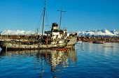 pic of tierra  - An old boat with Ushuaia and the mountains of Tierra del Fuego behind it - JPG