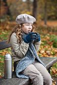 Girl In Winter Cloths Drinking From Flask Cup