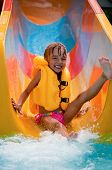 stock photo of inflatable slide  - Happy little girl on water slide at aqua park - JPG