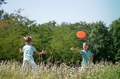 image of frisbee  - Happy boy and little girl playing frisbee on a meadow in a sunny day - JPG
