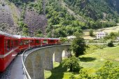 image of engadine  - Swiss mountain train Bernina Express passes the spiral of the Brusio Viaduct - JPG
