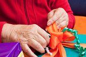 Senior Citizen Wrap Or Unpack Gifts, Closeup