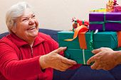 Female Senior Sits And Gets Or Give Many Presents