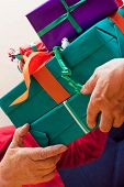 Senior Sits And Gets Or Give Many Gifts Closeup